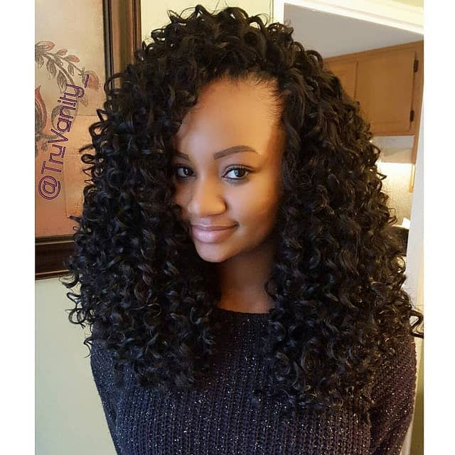 This is a highly voluminous curly style with loose curls at the bottom and super-poofed up hair at the top.