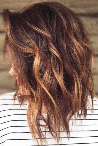 Auburn hair can also look really great with some blond highlights to freshen up your look. The elegant curls will also shine more with the color.