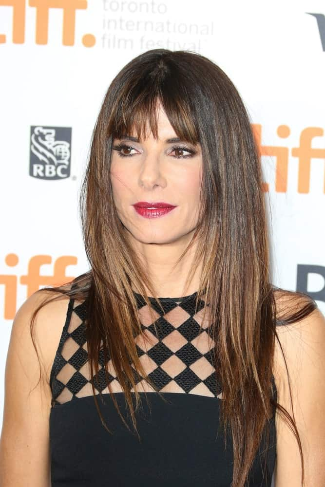 Sandra Bullock uses the short bangs to lay more emphasis to her best feature: those brown, intense eyes. They frame her face perfectly, making her cheekbones and jaw line pop. The honey highlights in her hair makes her look warm and friendly. It also has soft waves to it, which make the color look even better and gives it volume.