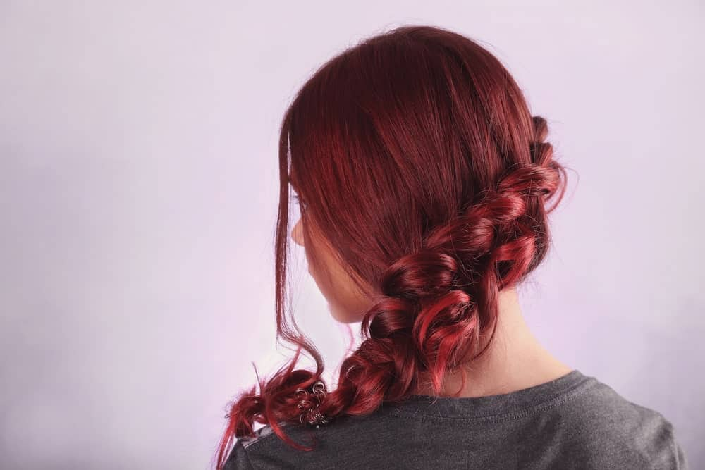 This beautiful hairstyle uses a flowing, loosely tied thick braid straight down the back of the neck. It has a carefree air about the hairstyle and highlights the different shades in the hair.