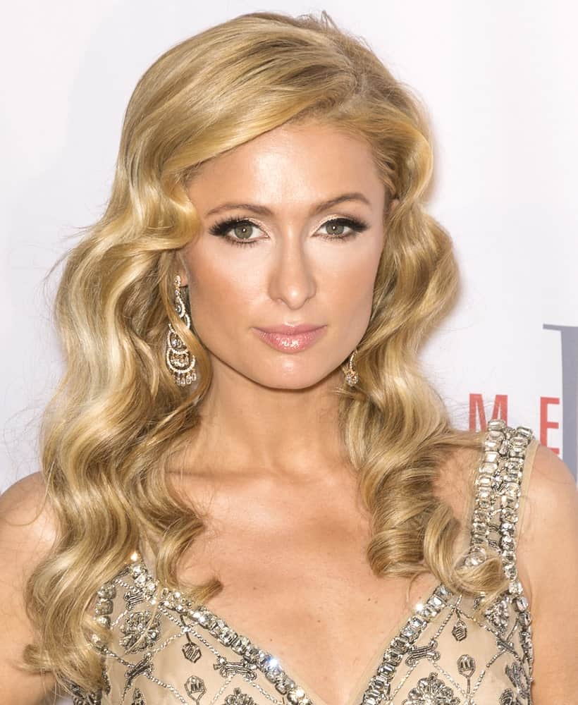 The granddaughter to the founder of the Hilton Hotels; Paris Hilton has always been under the spotlight, both because of her fashion style as much as for her scandalous behavior. Here, the socialite has added darker streaks of antique blonde to her golden hair. She has given her locks a side part and curled the layer into perfect, retro curls.