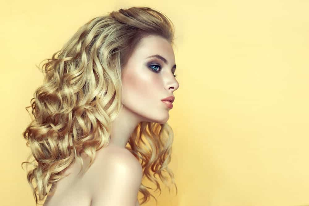 This is an absolutely gorgeous and voluminous layered look with golden-brown layers that have been curled all over and a mini poof on the top, making it look super unique and fancy.