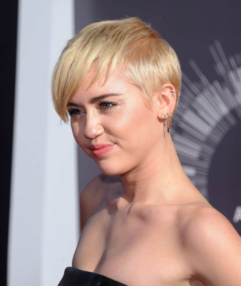 With this chic look, the fashionista, Miley Cyrus redefines short hairstyles with bangs. The hairstyle features short hair with one side of the head covered with heavy bangs. Without a doubt, this is one of the best ways to add elegance to short hairstyles.