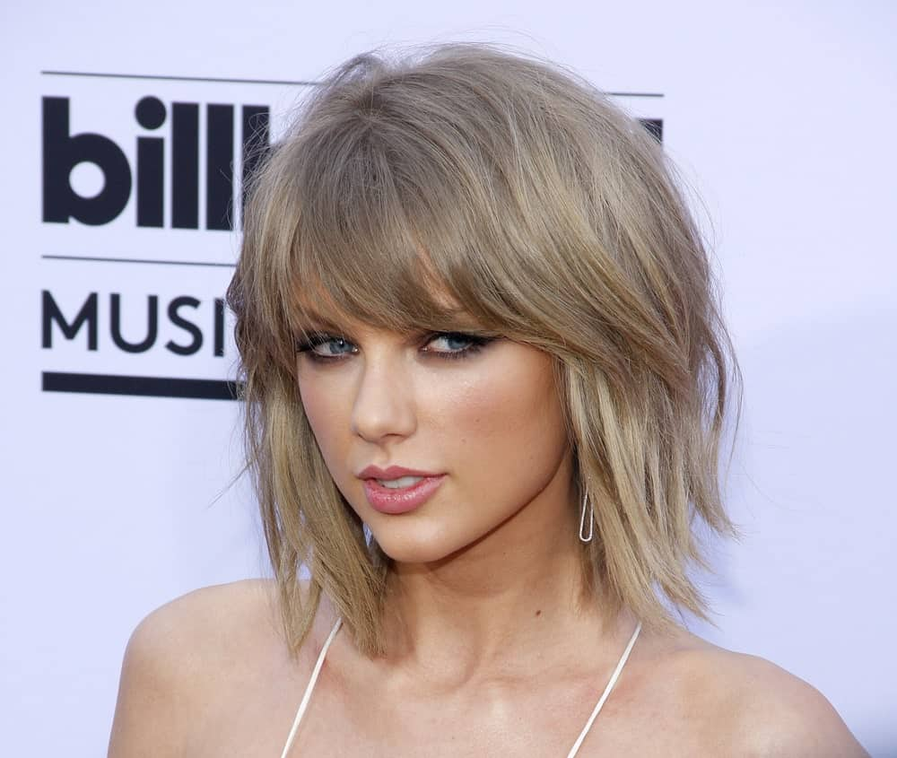 Taylor Swift is known for her blonde hair and bangs. She has been experimenting with short bangs for quite some time since they frame her face perfectly. They make her face look sharper and more attractive simply by attracting attention to her eyes, cheekbones, and perfect jaw line.