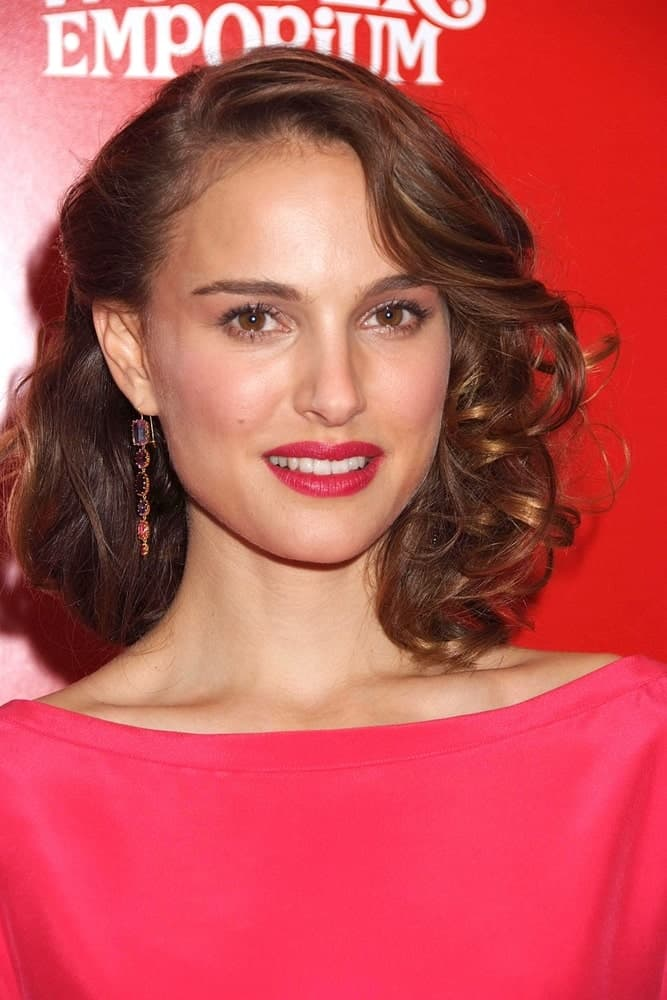 One side of Natalie Portman's bangs has been straightened and then curled at the end. It compliments tightly curled hair in the perfect way. The other side of her bangs has been clipped in a slightly puffy way.