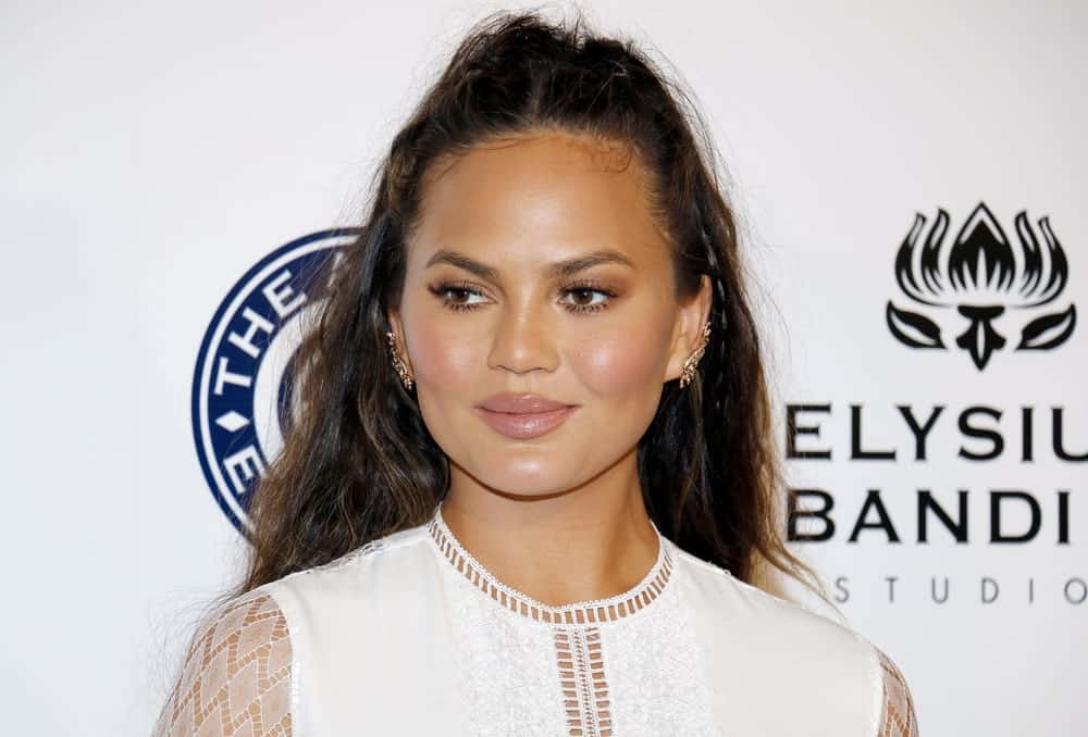 Want to look casual but elegant at the same time? Try going for Chrissy Teigen's look. The model tightly pulled back the hair from the front and the side of her head into a messy updo. She then let the rest of her beautiful long hair fall down her back. The style looks great with messy, ruffled hair, so keep the brushing to the minimum.