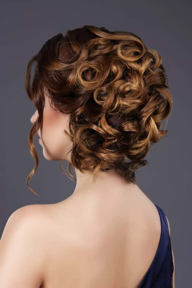 Elegant up dos with curls have been the signature look for any formal event. The wavy hair framing your face with the auburn color is a match made in heaven.