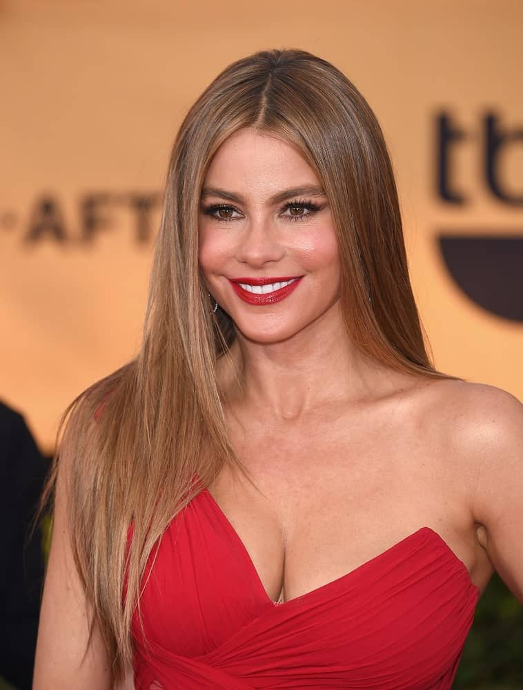When you have hair as silky, glossy and long as Sofia Vergara, it is best to keep them loose. Ask your stylist to iron out your hair to a slick-straight style and part it in the middle like Vergara. For some wow factor, add some highlights or balayage to your hair.