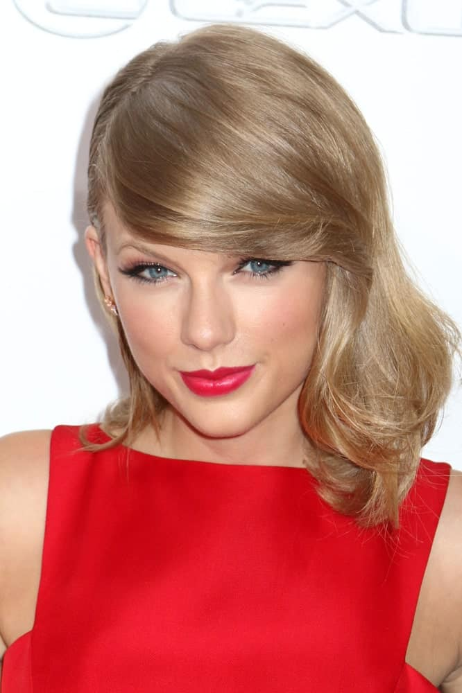 The sleek, straight long side bangs are neatly tucked into the rest of Taylor Swift's hair. The hair is straight from the top but ends in a big curl that looks perfect on her.