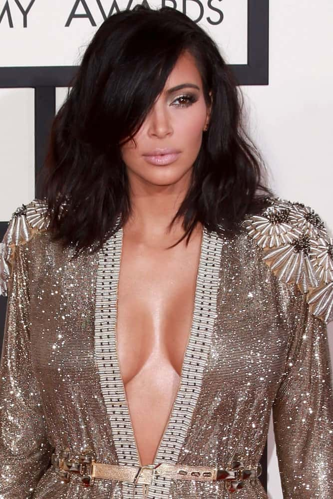The heavy, thick side bang swept to the side pair perfectly with the messy bob framing Kim Kardashian's face. The untidiness of the hair adds to the volume and will attract attention to your cheekbones and jaw line.