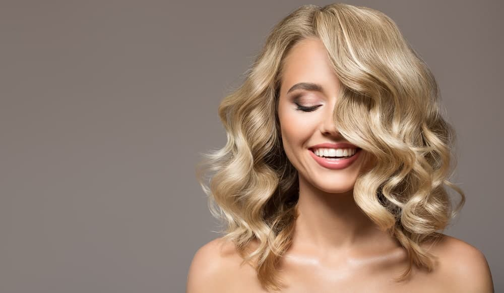 If you have blonde and slightly curly hair, this hairstyle is a great fit with perfect curly layers and a side-parting.