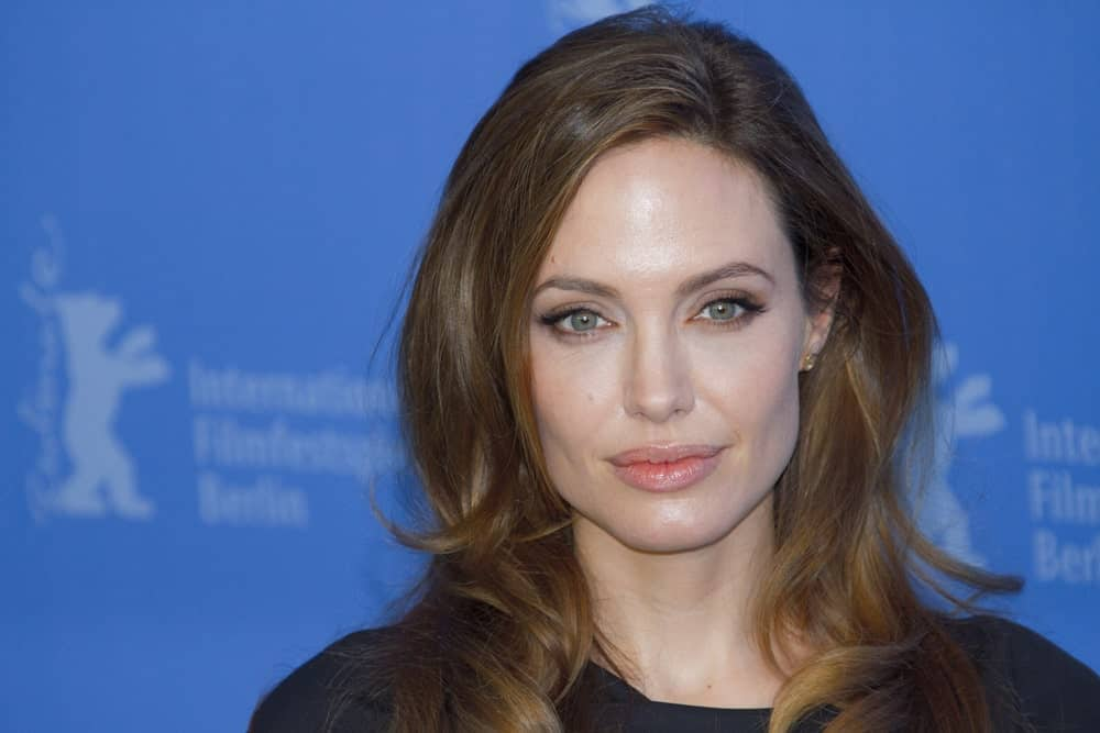 Angelina Jolie can be seen here supporting loose curls with a straight, long side bang. The dark brown hair ends in blonder tips giving it an irresistible gradient.