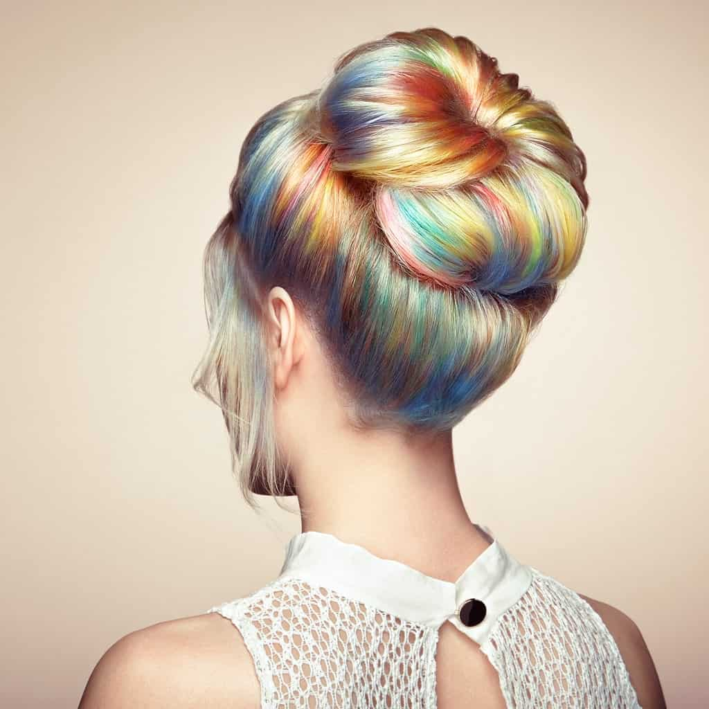 If you are in the mood for having some fun with your long hair, then pastel rainbow highlights might just be the thing for you. Wear your dyed hair in a high donut bun to let those colors dazzle everyone.