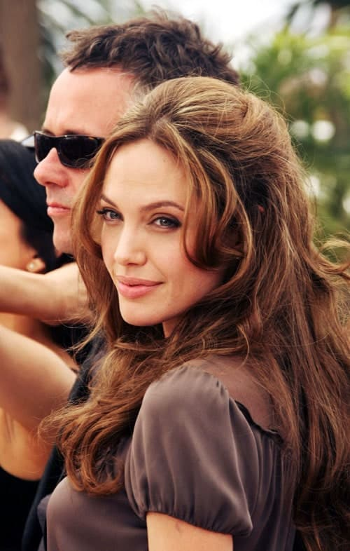 Angelina Jolie's side bangs are parted in the middle with the hair right above it puffed up. The rest of the hair is loose and slightly wavy.