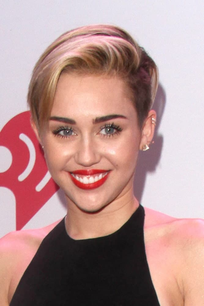 Miley Cyrus started the trend of sweeping your hair in one swoop onto the side. She looks absolutely stunning with the red lipstick, long lashes, and thick eyebrows.