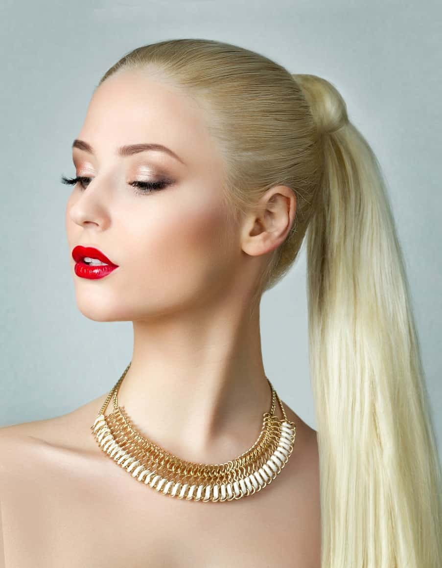 Wear your gorgeous straight hair in a long ponytail like this model. Wrap a strand around the hair band to cover it, giving it an exquisite look. Plain hairstyles like this are best accentuated by bright lip color and a few accessories.