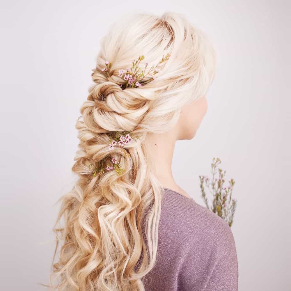 Nothing says elegance like this hairstyle for long and blonde curly hair. It features hair cut in layers and gathered at the back of the head where the top layer forms a loose half-braid. The rest of the hair simply flows down the shoulders and over the back. In the front, side bangs perfectly frame the face to bring out the eyes. This hairstyle gives you a lot of options for decorating your hair. Whether you put in flowers of some fancy clips, you are bound to look stunning. The cherry on top – you won't have to worry about loose strands going into your eyes when you rock this hairstyle.
