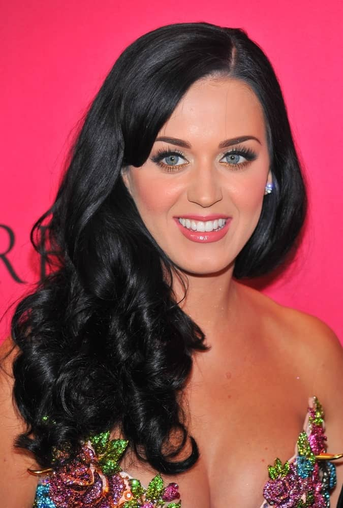 Katy Perry displays her great hairstyle that you are sure to fall in love with. Notice how she pairs the side-swept bangs with thick, voluminous curls all pushed to one side for a dazzling look.