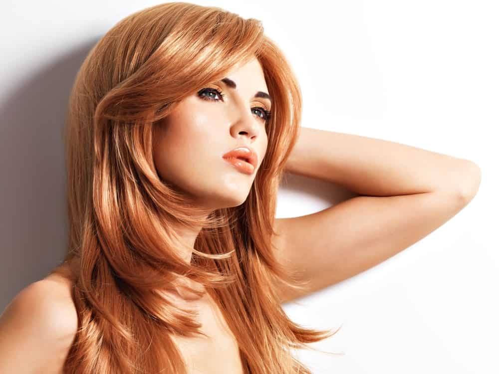 This hairstyle is simply stunning with straight reddish hair and beautiful layers coming from a side parting all the way down. The layers on the top are styled inwards while the ones towards the bottom have a straighter look.