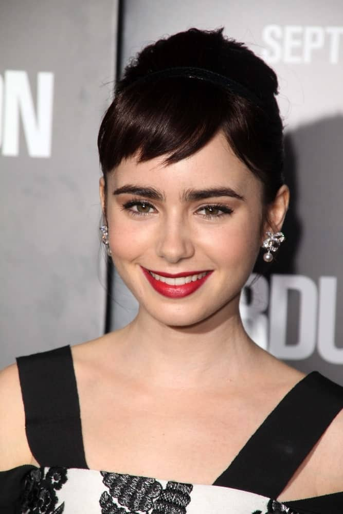 Lily Collins uses short, straight bangs to highlight her cheekbones and gorgeous clear skin in the most perfect way possible. The rest of her hair is in an elegant bun, which emphasizes her long neck and collarbones. The whole hairstyle is a great example of how amazing short bangs can look.
