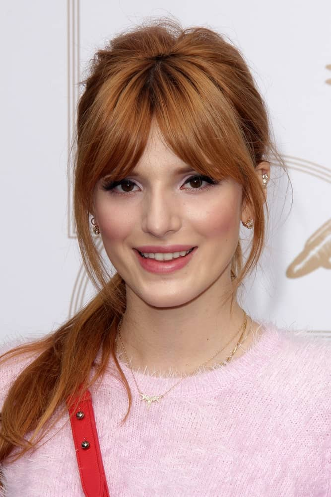 Bella Thorne could not look anymore lovelier than this! She is sporting long hair tied in a pony and heavy front bangs parted in the middle. While the short bangs cover most of the forehead, her face is framed by the chin-length layers. To complete the look, the ponytail is casually thrown to the front on one side.