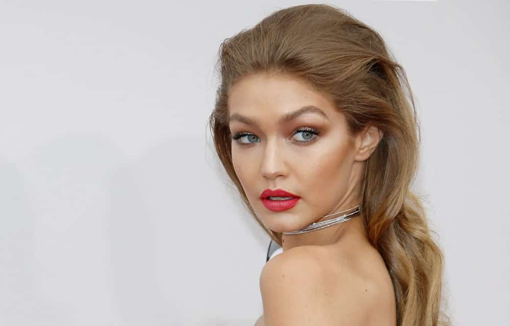 A lot of people are afraid of teasing their hair and for good reasons. However, if you are Gigi Hadid, this is the perfect way to do it. The supermodel has combed back her hair with some subtle backcombing and gave her gold-highlighted waves some loose curls. The light brown pushed-back hair enhances her pretty face shape and cheekbones. If you want to try the look without risking hair breakage, add weaves or hair fibers and invest in a hair thickening serum.