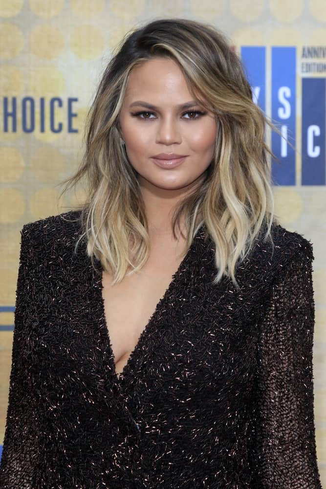 The side bangs are swept to one side, so that the hair looks like it is flowing in the wind. The messy waves in the hair paired with the blond tones look elegant.