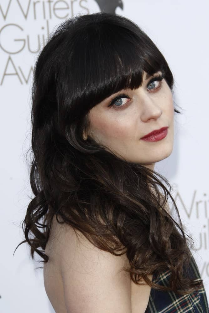 Zooey Deschanel is a true advocate of bangs. In fact, she has been sporting bangs for years! Check out this simple yet stunning hairstyle featuring blunt bangs and medium-length hair with loose curls. As the bangs frame the face from the top, the hair is casually tousled on the shoulder on one side, resulting in a subtle and natural look.