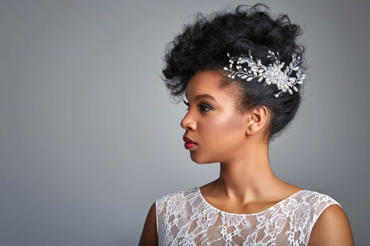 Tight coils can be piled on the top while the sides are framed with pretty flowers. This is the perfect look for a bride or for a formal event.