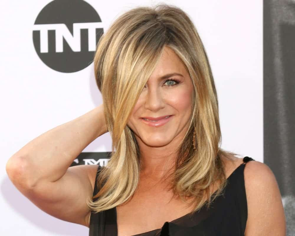 "Jennifer Aniston may be the queen of layered hairstyles. Since her days on ""Friends,"" the actress has rocked multiple variants of the layered cut — and she hasn't lost her edge. The actress is sporting a sleek layered lock, with side-swept bangs that cover one of her eyes. The look is very chic."