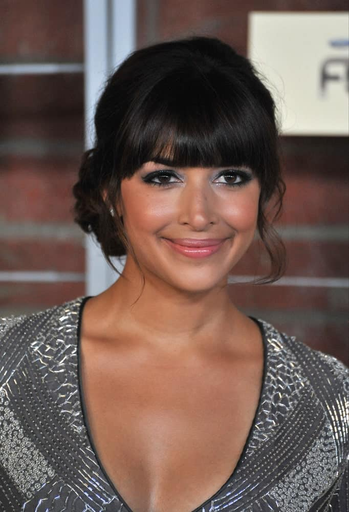 Check out the stunning look of Hannah Simone. The hairstyle features straight cut blunt bangs. The hair is loosely tied in a bun at the back while a few loose, slightly curly strands of hair frame the face from both sides to complete the look. If you are aiming for a soft, lovely look, this is the hairstyle for you!