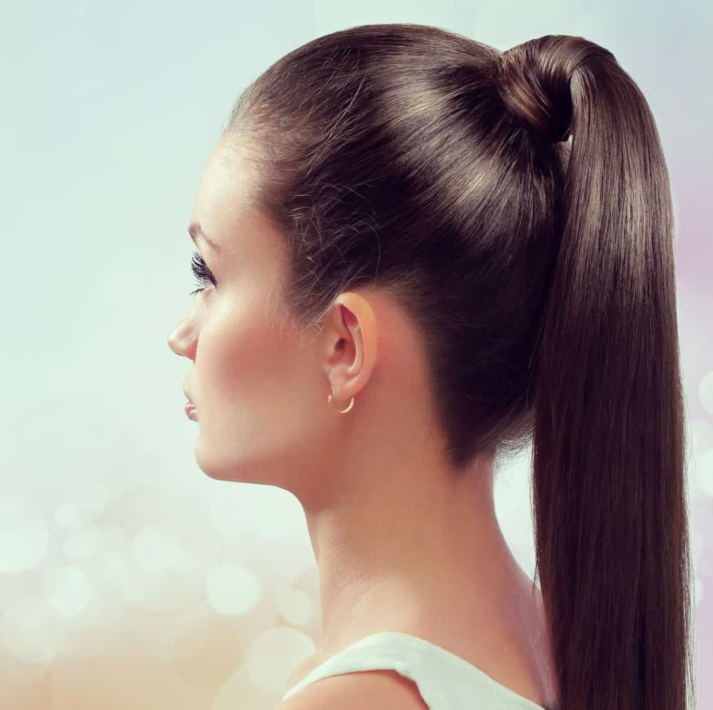 "If your hair is silky straight and brunette, this is the hairstyle for you! The hairstyle features long brunette hair tied in a high ponytail at the back. However, if you look closely, it is no ordinary ponytail. Thick and lustrous locks of hair replace the hair tie and hold the rest of the hair in place. This is one of the ""neat"" hairstyles that make sure you don't have to wipe out hair out of your face and eyes every two seconds. Whenever you are in a hurry but want to look your best, go for this sleek and stylish ponytail."