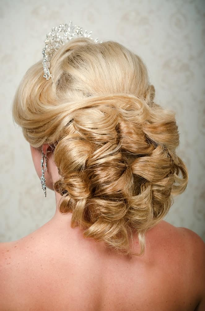 Want to feel a little fancy? Go for the ultimate princess look with this hairstyle! It features long blonde hair. This hairstyle works best when your hair has a loose curly texture. It gathers your hair at the back in a loose bun. However, as you can see, it is no ordinary bun! The strands of your blonde hair need to go around in loops to create this beautiful look. In the end, slay the look by adding a tiara. With this hairstyle, you can be the queen that you are! Do keep in mind that while this hairstyle offers a classic bridal look, it is equally good for prom night, date nights, or any other formal event!