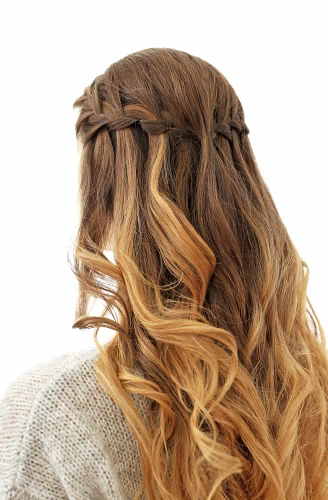 This is the most romantic looking braided hairstyle ever.  First, part your hair from the middle. Take a few hair strands from your right section and divide it further into three sections. Cross the top side of the section over the middle one which will hang loosely to create a waterfall look.  Do the same with the bottom side with new middle hair strands, repeat the process until you have reached the end of your hair length.