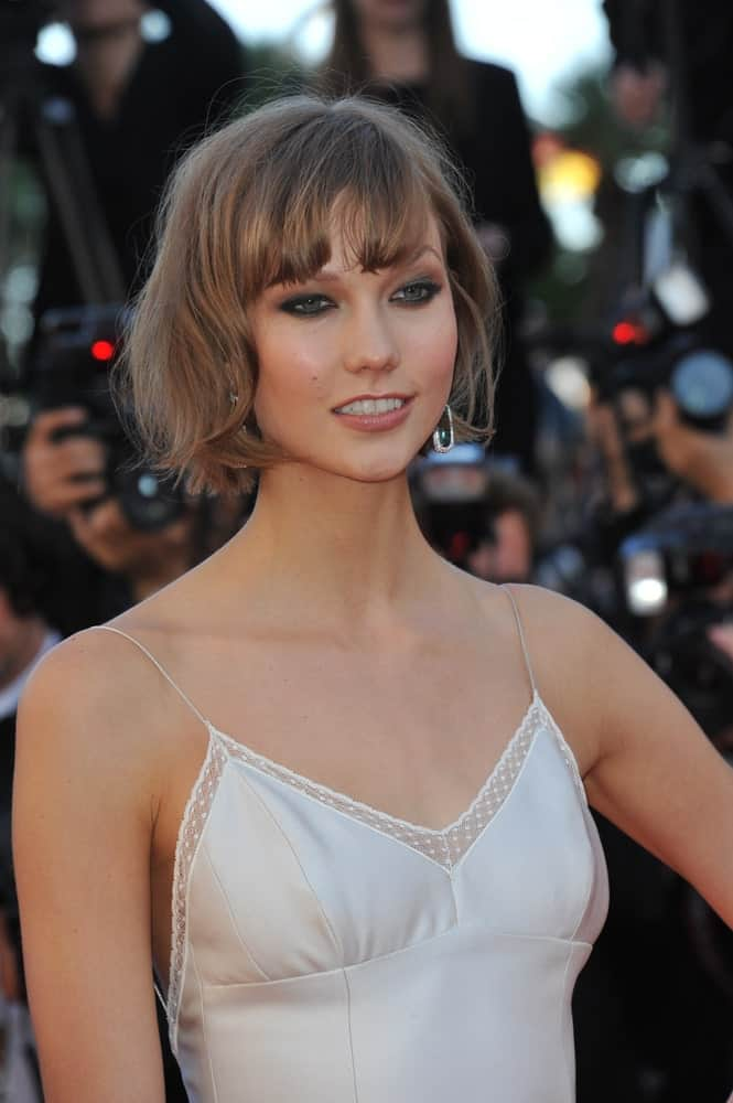 Karlie Kloss is seen here supporting a short bob with gorgeous bangs. They are accentuated by the soft brown color of the hair and frame her face perfectly. The short bob, combined with the bangs, emphasizes the neck making it seem longer.