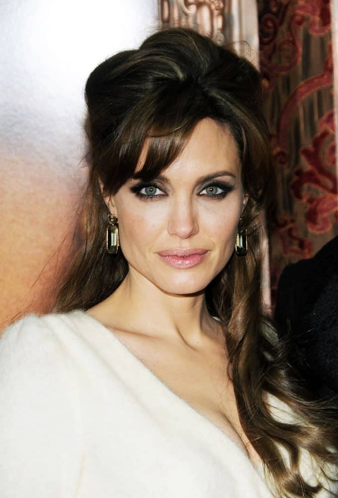 When you feel like having a hairdo for a night, consider this hairstyle if you have long brunette hair. Sported by Angelina Jolie, the hairstyle features brunette locks coupled with bangs. The hair is tucked at the back to create volume at the top. The side bangs work to frame the face and bring attention to the eyes as the rest of the hair falls loosely around the shoulders to create this elegant look. It also gives you the perfect opportunity to show off your earrings.