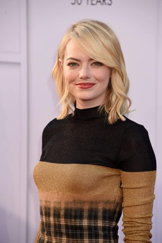Emma Stone manages to look exceptionally effortless with the straight long side bangs ending in the perfect curl against her blond hair.