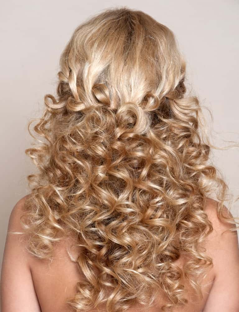 Nothing can beat this hairstyle in cuteness because it's just so adorable. Plus, it is perfect for all occasions – from weddings to a beach day, this hairstyle offers just the right look. It features long curly blonde hair that is set in a loose and messy, stylish braid at the back of the head. Below the braid, the curls hang down the shoulder, reaching to the back. This hairstyle offers the perfect opportunity to showcase your majestic curls without overdoing it. In the front, it perfectly frames your face while making sure yours stay out of your face. Keep in mind that contrary to how it looks, the hairstyle is relatively easy to create and with a little practice, you can master it in no time!