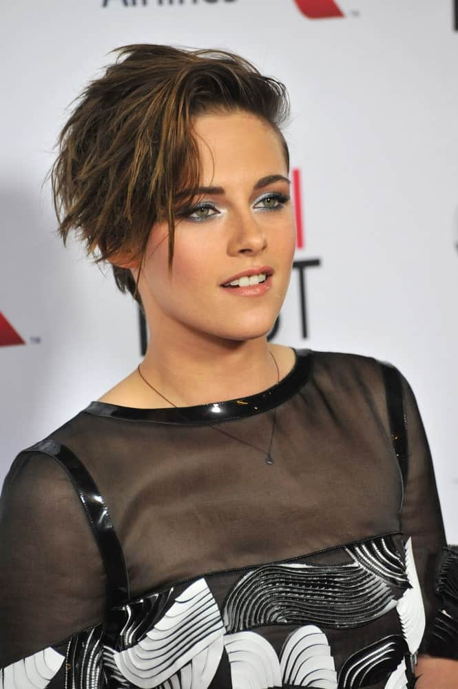 Here we see Kristen Stewart look super chic and trendy in a side-swept bangs hairstyle. The hairstyle features rugged and unruly bangs that give a wild, frenzy touch.