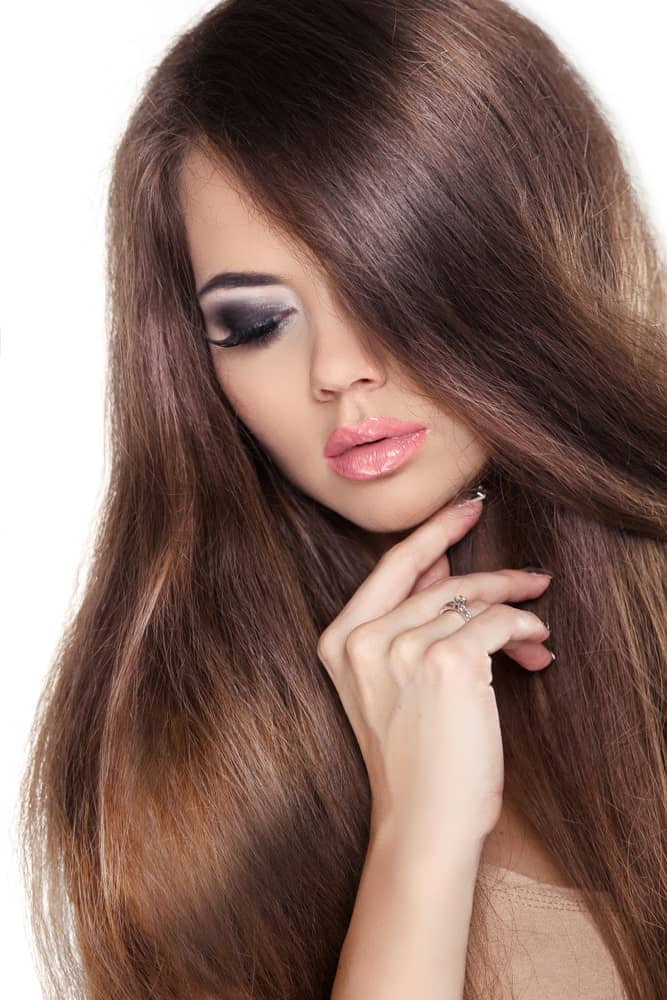 This is a super voluminous straight hairstyle with a side parting that appears to cover half the face from one side and have been let loose from the other side.