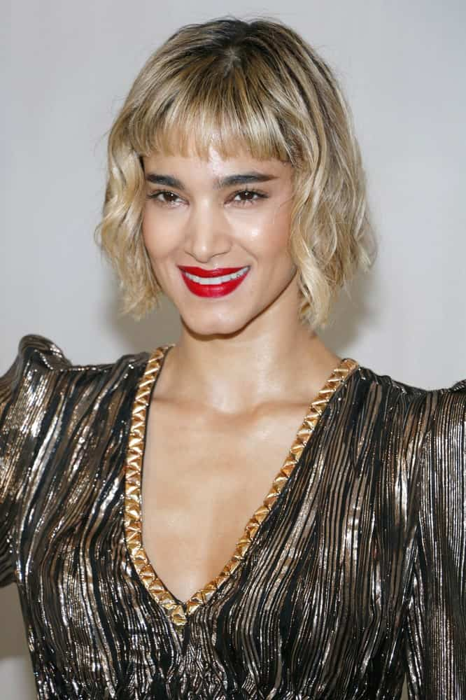 Looking for a new, stylish look to go with your short blunt bangs? Go for curly, tousled hair! Modeled by Sofia Boutella, this hairstyle features short blunt bangs, covering only half of the forehead. The bangs are coupled with chin-length curly hair. Whether you carry an ordinary straight bob or go for an asymmetrical bob, blunt bangs look good with all!