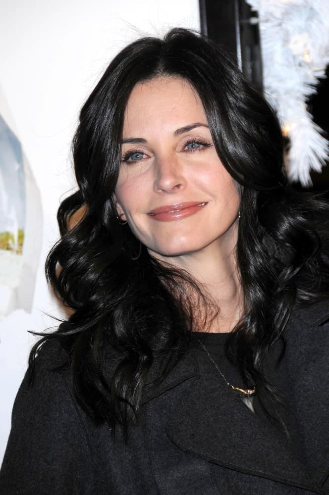 "This is the famous TV star from the series ""Friends"", Courtney Cox. She is carrying gorgeous big loose curls and a parting in the middle."