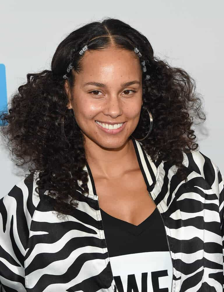 Alicia Keys channeling her inner hippie with her thick, curly hair parted in the center and incorporated with some twisted styles.
