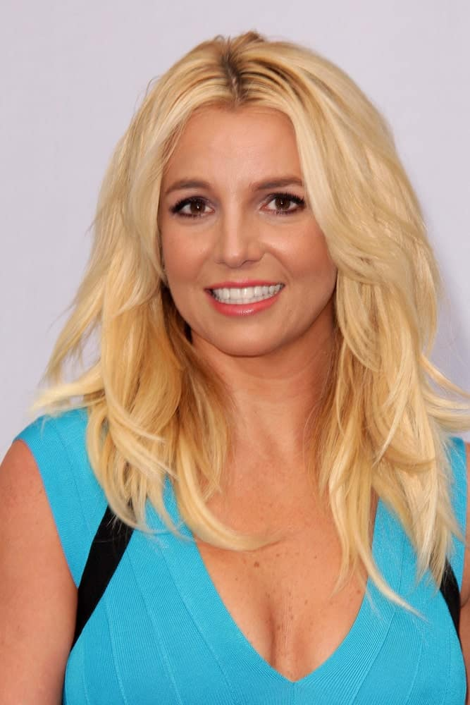 Here's Britney Spears with her famous blonde hair cut medium-length in 2013 layered and slightly wavy.  She's sporting a blue top.