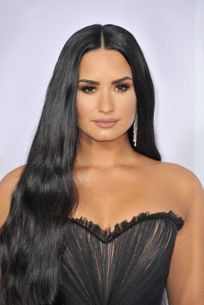 Demi Lovato is like a regal goddess with this hairstyle! Her center-parted, long and black hair is loosely set above her right shoulder. This one frames the shape of her face perfectly
