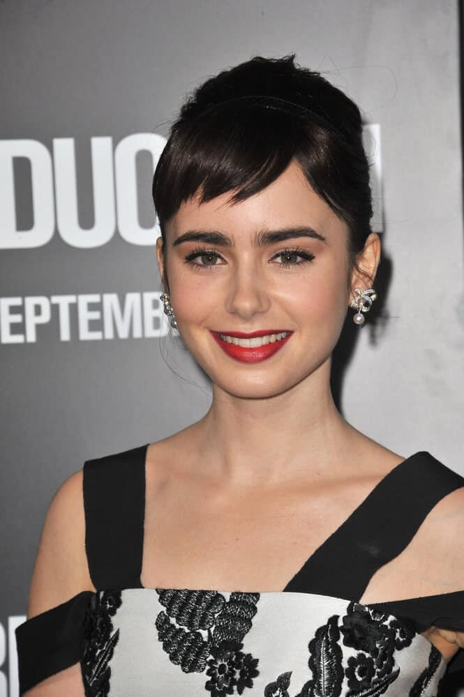 The red-lip, classic look is Lily Collins' trademark! Her iconic look goes well with this retro upstyle with short, side-swept bangs.