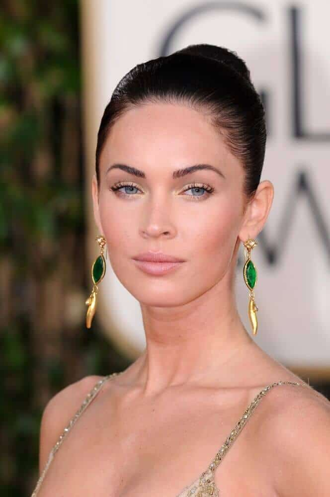 Megan fox looking extra elegant with her black hair styled into a sleek and tight bun, showcasing her facial assets.