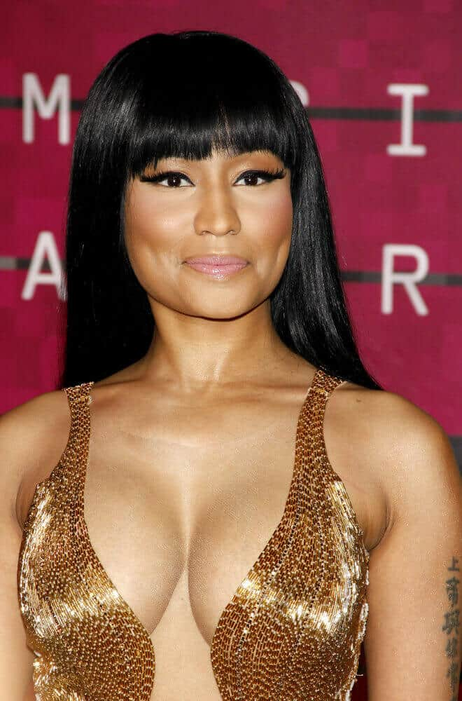 Nicki Minaj with her long and thick, black hair flowing down her back. The simple hairstyle is paired with blunt bangs for a preppy look.