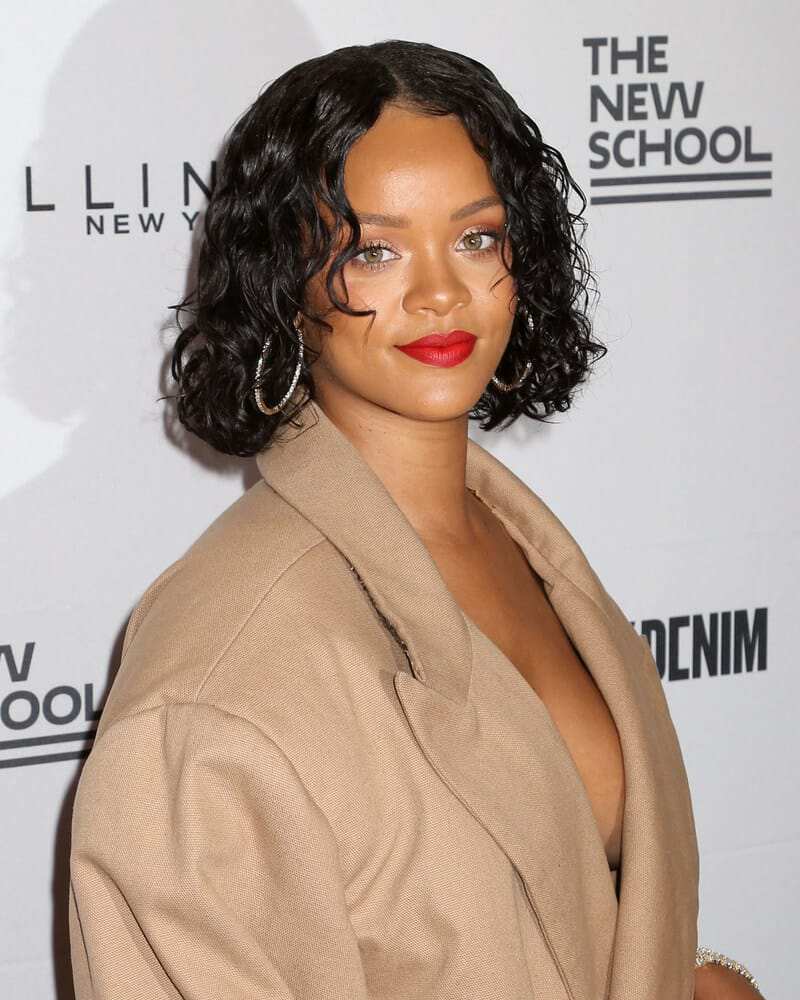 Rihanna sporting a carefree look with her curly bob, styled with hair mousse for a maintained finish.