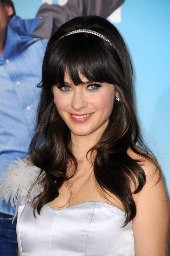 Zooey Deschanel's wavy hair with thick, blunt bangs embellished with a pearl headband.